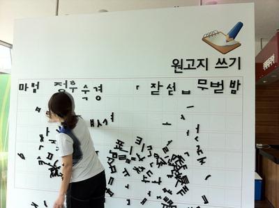 원고지 쓰기 벽에 자석으로 된 글씨를 붙이고 있다.
