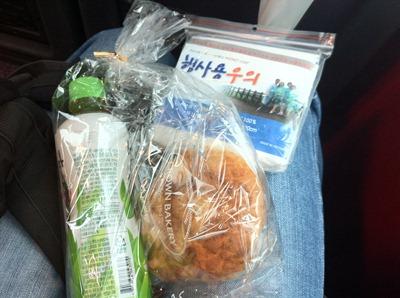 무릎 위에 올려 놓은 음료, 빵, 비옷