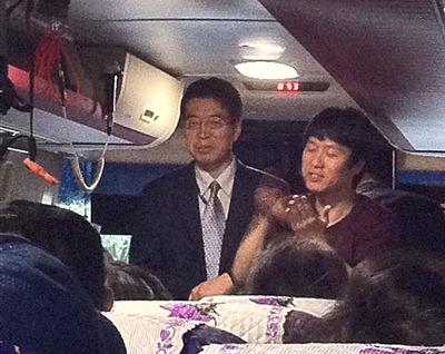 버스 안에서 좌측에는 관장님이 안내말씀을 하시고 우측에서 수화통역을 하고 있다.