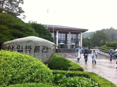 산림박물관이라고 새겨진 자연석과 뒤에 보이는 박물관 건물